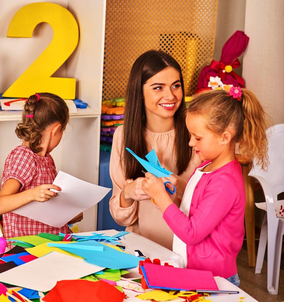 Niñas y mamá recortando papeles de colores