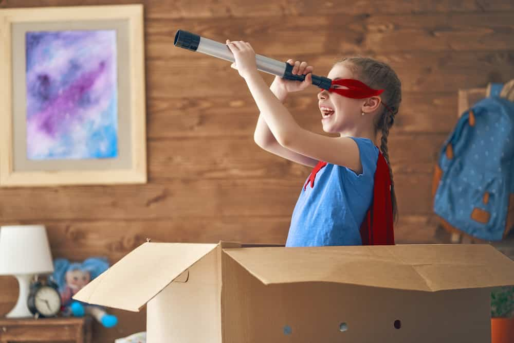 Niña disfrazada de superhéroe metida en caja de cartón