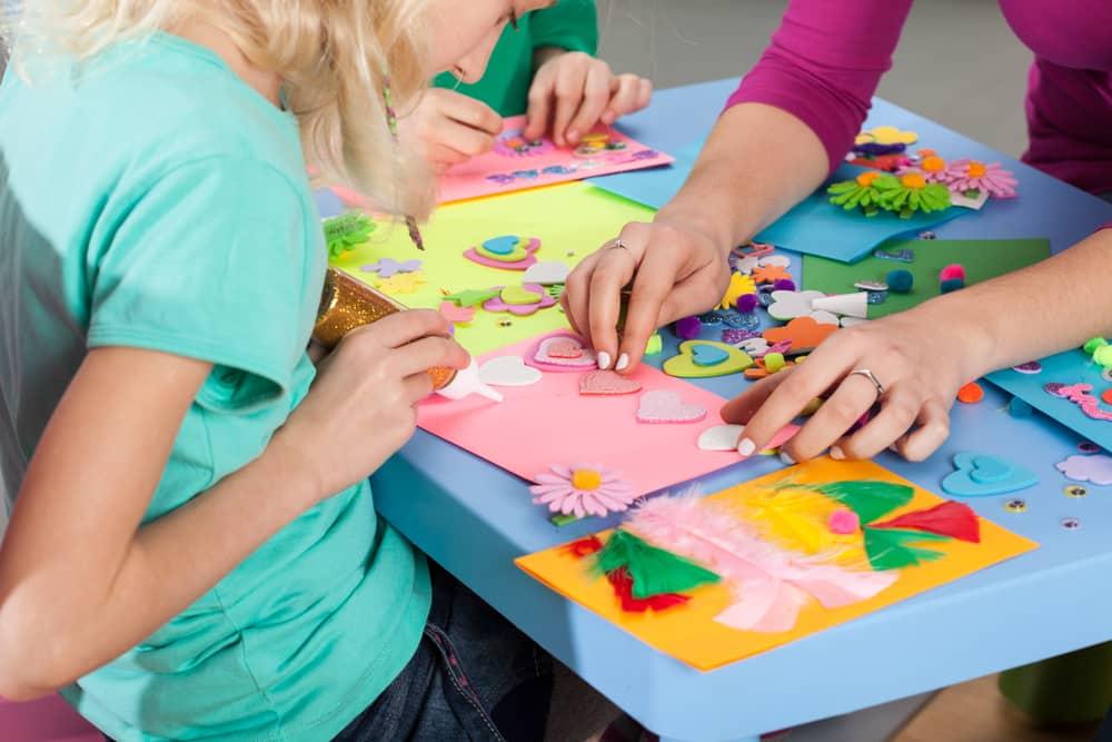 Detalle de manualidades hechas por niños y adulto con papeles recortados