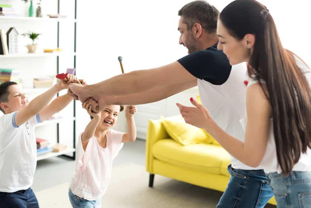 Papá y mamá jugando en casa con niños