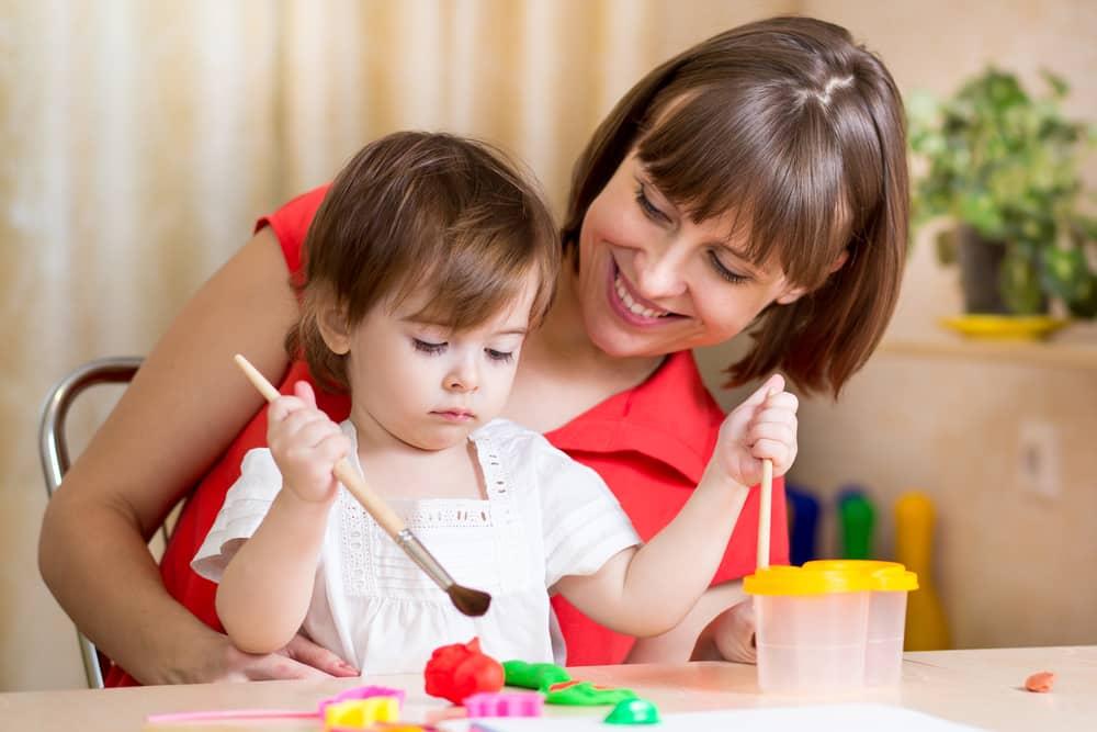 Niña y mamá jugando con plastilina en casa