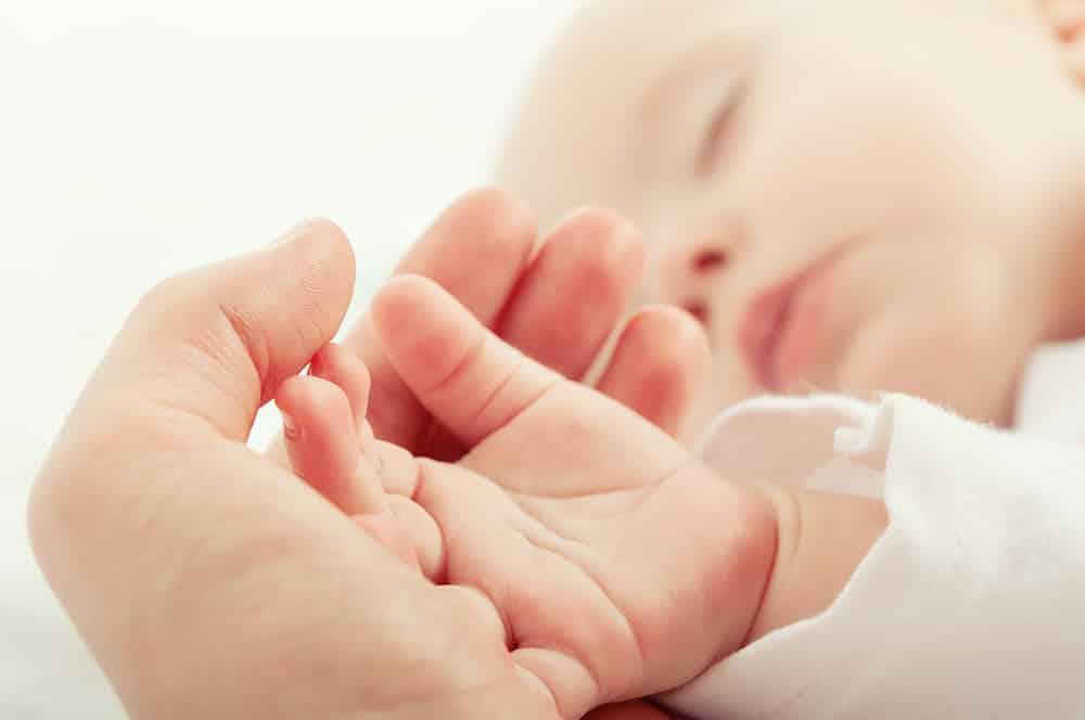 Bebé durmiendo, cogido a la mano de su madre