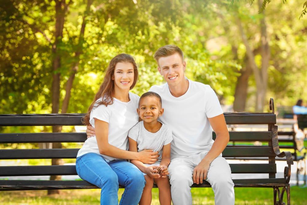 Joven pareja con niños adoptado. sentados en un parque